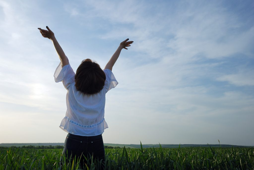 The girl on a field. The woman with the lifted hands to the sky on a green meadow